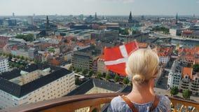 Uma mulher com a bandeira de Dinamarca em sua mão limpa para fora sobre à cidade de Copenhaga, está na torre antiga com uma espir vídeos de arquivo