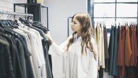Uma mulher com cabelo marrom está escolhendo a roupa comprar em uma loja Fotos de Stock