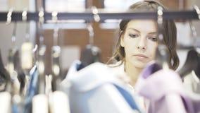 Uma mulher com cabelo marrom está escolhendo a roupa comprar em uma loja Retrato Fotografia de Stock Royalty Free