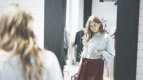 Uma mulher com cabelo marrom está escolhendo a roupa comprar em uma loja Retrato Fotografia de Stock