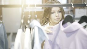 Uma mulher com cabelo marrom está escolhendo a roupa comprar Loja do desenhista Imagem de Stock Royalty Free