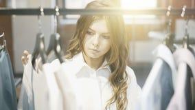 Uma mulher com cabelo marrom está escolhendo a roupa Loja do desenhista Imagens de Stock
