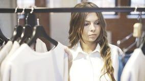 Uma mulher com cabelo marrom está escolhendo a roupa Loja do desenhista escolha Fotografia de Stock