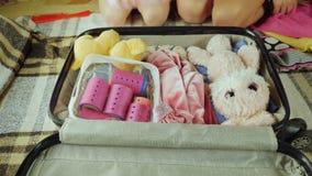 Uma mulher com uma criança está embalando coisas em uma mala de viagem para viajar Puseram a roupa e os brinquedos lá Feriado com video estoque