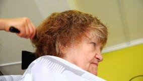Uma mulher com enrugamentos por um cabeleireiro Doing um corte de cabelo filme