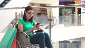 Uma mulher com uma inabilidade em uma cadeira de rodas usa o telefone na alameda após a compra Fim acima video estoque