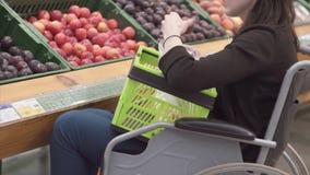 Uma mulher com uma inabilidade em uma compra da cadeira de rodas no supermercado escolhe frutos e põe-nos em um pacote Fim acima video estoque