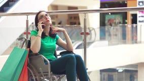 Uma mulher com uma inabilidade em um divertimento da cadeira de rodas que fala no telefone na alameda após a compra Fim acima vídeos de arquivo
