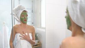 Uma mulher com uma máscara hidratando verde em sua cara vê-se de repente no espelho e é amedrontada vídeos de arquivo