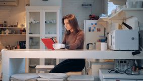 Uma mulher com uma mão protética está trabalhando com uma tabuleta em uma cozinha