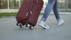 Uma mulher com uma mala de viagem que dirige à construção do aeroporto Close-up dos pés video estoque