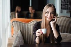 Uma mulher com o sorriso bonito que tem a conversação de telefone celular ao descansar após o dia do trabalho no café imagens de stock