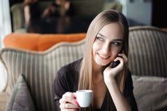 Uma mulher com o sorriso bonito que tem a conversação de telefone celular ao descansar após o dia do trabalho no café fotos de stock royalty free