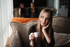 Uma mulher com o sorriso bonito que tem a conversação de telefone celular ao descansar após o dia do trabalho no café foto de stock royalty free