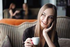 Uma mulher com o sorriso bonito que tem a conversação de telefone celular ao descansar após o dia do trabalho no café fotografia de stock royalty free