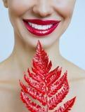 Uma mulher com os bordos vermelhos sensuais e uma samambaia fotos de stock