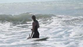 Uma mulher com uma ressaca no mar e espera de uma onda video estoque