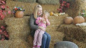 Uma mulher com sua filha pequena está sentando-se no feno e está alimentando-se um porco pequeno com legumes frescos vídeos de arquivo