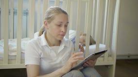 Uma mulher com uma tabuleta eletrônica em suas mãos senta-se ao lado de um bebê pequeno de sono em uma ucha do bebê filme