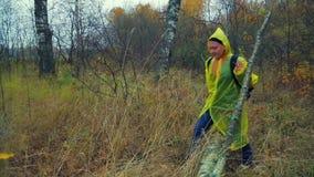 Uma mulher com uma trouxa em etapas amarelas de uma capa de chuva sobre uma árvore caída na floresta filme