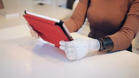 Uma mulher com um braço robótico está operando uma tabuleta vídeos de arquivo