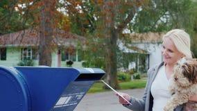 Uma mulher com um cão em seus braços aproxima uma caixa postal na rua e joga uma letra nela vídeos de arquivo