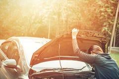 Uma mulher com um carro quebrado e abrem a capota fotografia de stock royalty free