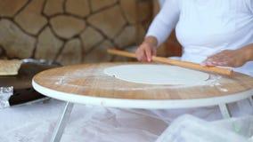 Uma mulher com um pino do rolo desenrola a massa para o bolo Desenrole a massa com um pino do rolo O processo de filme