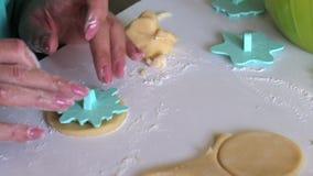 Uma mulher com um selo aplica o ornamento em placas redondas da massa rolada Para fazer sandu?ches do marshmallow filme
