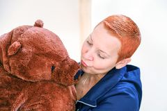 Uma mulher com um urso de peluche Mulher que beija o urso de peluche isolado no fundo claro imagem de stock