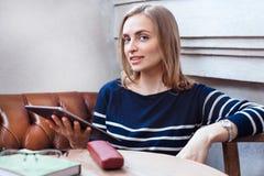 Uma mulher com uma tabuleta em um café Uma moça sorri Estilo de ensino ocasional urbano e relaxamento nos cafés Fotografia de Stock