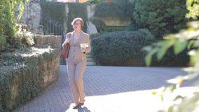 Uma mulher com uma vara do selfie anda ao longo de um trajeto vídeos de arquivo