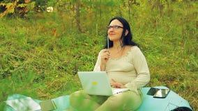 Uma mulher com vidros na borda de uma floresta com um lápis em sua mão e em um portátil pensa sobre o projeto video estoque