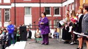 Uma mulher completa no suporte do microfone dá um discurso à audiência na rua video estoque