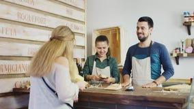 Uma mulher compra o queijo em uma loja pequena da família conceito da empresa de pequeno porte