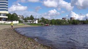 Uma mulher corre no dia o litoral ou o movimento lento do lago vídeos de arquivo