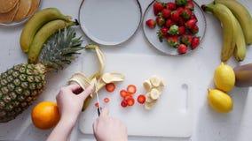 Uma mulher corta bananas em uma placa de corte video estoque