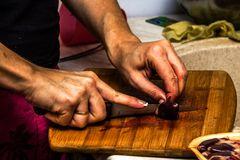 Uma mulher corta corações da galinha com uma faca foto de stock royalty free