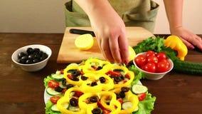 Uma mulher corta um limão e espreme-o em seu suco em uma placa com uma salada vegetal Close-up filme