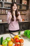 Uma mulher corta um pepino na cozinha com uma faca Preparação da salada A morena mostra o polegar imagens de stock