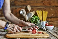 Uma mulher corta um tomate de cereja e prepara uma massa italiana tradicional imagens de stock