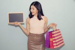 Uma mulher da beleza que olha assina dentro sua mão e sacos de papel guardar foto de stock