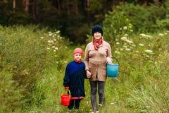 Uma mulher da idade da reforma e um menino de sete anos nas madeiras com as cubetas dos cogumelos fotografia de stock