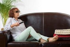 Uma mulher da tevê madura do relógio da idade com vidros 3D Fotos de Stock