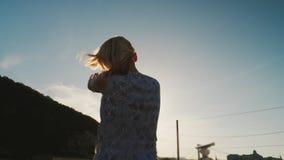 Uma mulher dança em um iate, contra o contexto do sol de ajuste Aprecie um cruzeiro do rio ou do mar, partido no navio video estoque
