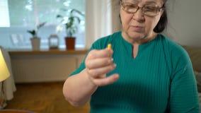 Uma mulher das pessoas idosas mede a pressão sanguínea e toma comprimidos em casa vídeos de arquivo