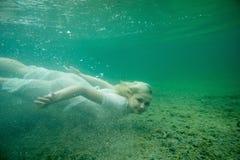 Uma mulher de flutuação Retrato subaquático Menina na natação branca do vestido no lago Plantas marinhas verdes, água imagem de stock