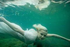 Uma mulher de flutuação Retrato subaquático Menina na natação branca do vestido no lago Plantas marinhas verdes, água Fotografia de Stock Royalty Free