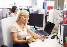 Uma mulher de funcionamento que come o almoço usando o telefone esperto, telefone em sua mesa Fotografia de Stock Royalty Free