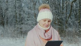 Uma mulher de meia idade anda em um parque do inverno, aprecia uma tabuleta filme